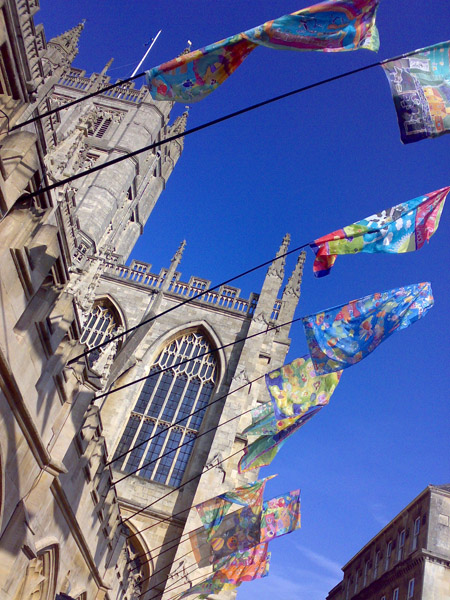 Bath Abbey with colourful flags.